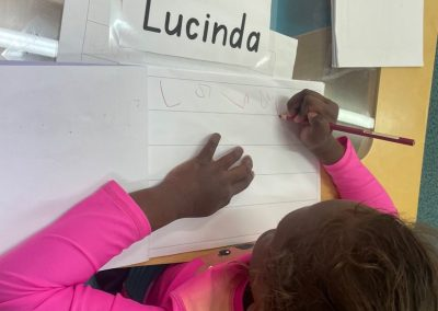 Student writing her name on piece of paper